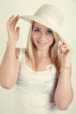 Young blond girl wiyh white hat and dress Stock Photography