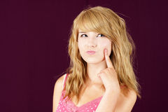 Young blond girl wondering. Funny portrait of a wondering or thinking  pretty young blond teenager girl with finger on cheek over purple or deep red background Stock Photos