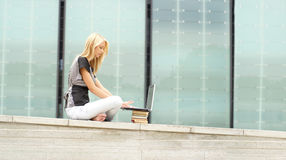 A young blond girl is working on the laptop Stock Image