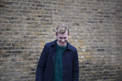 Young blond guy in front of brick wall Royalty Free Stock Photography