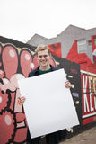 Young, blond guy holding blank sign. Hipster in front of edgy graffiti wall holding white message board stock photos