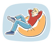 Young blond guy resting on a bean bag chair. Young blond guy sitting comfortably on a bean bag chair, relaxing, thinking and dreaming Royalty Free Stock Photo