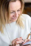 Young blond hair business woman writing a text message using mes Royalty Free Stock Photography