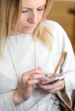 Young blond hair business woman writing a text message using mes Royalty Free Stock Image