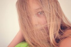 A young blond hair girl portrait with messy hair. A teenager is hiding the photographer behind her long hair. A young blond girl portrait with messy hair. A royalty free stock photography