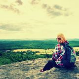 Young blond hair Woman hiker takes a rest on peak of the Mountain Stock Photo