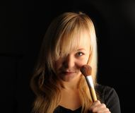 Young blond hair woman portrait  with make-up brush on dark background Royalty Free Stock Photography
