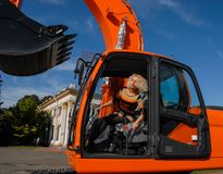 A young blond hair woman sits in a cabin of a new orange crawler excavator with a big black bucket. A young blond hair woman sits in a cabin of a new orange Stock Photo