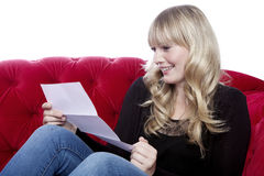 Young blond haired girl read a letter on red sofa in front of wh Stock Photos
