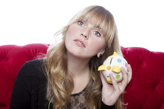 Young blond haired girl on red sofa hears coins in piggybank in Stock Images