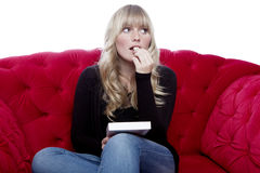 Young blond haired girl taste chocolate on red sofa in front of Royalty Free Stock Photography