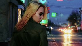 Young blond haired woman in nights street looking back toned shot. Blurred carlights on background stock video