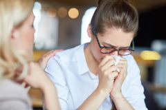 Please do not cry!. Young blond-haired women comforting her upset best friend, she wiping nose with handkerchief, blurred background Stock Photos