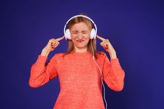 Young blond listening loud music. Isolated on violet background Stock Photography
