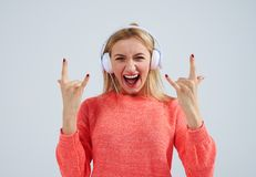 Young blond listening rock music in headphones. On white Stock Image