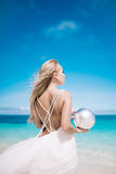 Young blond long hair bride wear a white open back wedding dress and stand on the white sand beach with a pearl. Looking to the se stock photography