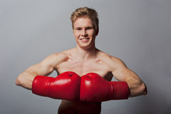 Young blond man with boxing gloves Royalty Free Stock Photo