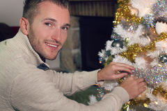 Young blond man decorating a Christmas tree Stock Image
