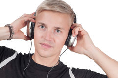 Young blond man in headphones watching on you Royalty Free Stock Photography