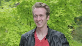 Young blond man in leather jacket standing outside and smiling at camera stock video footage