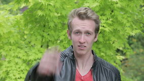 Young blond man in leather jacket standing outside and talking upset into camera stock video footage