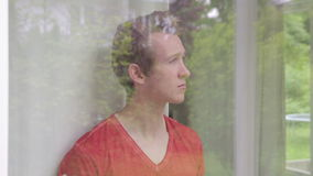 Young blond man looking out of window and holding a cup stock video