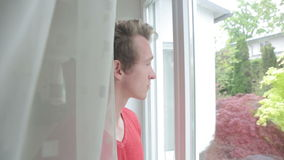 Young blond man looking out of window and holding a cup stock footage