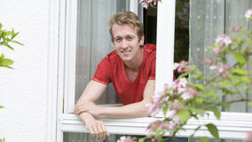 Young blond man looking out of window Stock Image