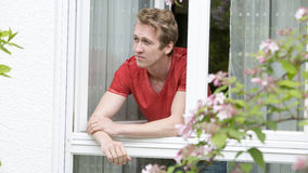 Young blond man looking out of window Stock Photos
