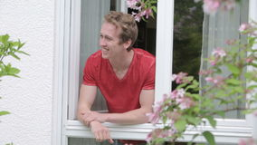 Young blond man opens window and greeting someone with a smile stock video