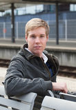 Young blond man in railway station royalty free stock photo
