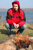 Young blond man in red jacket sit near fire. Royalty Free Stock Photos