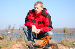 Young blond man in red jacket sit near fire. Royalty Free Stock Images