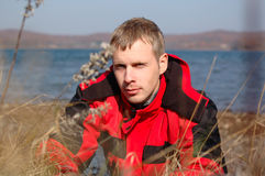 Young blond man in red jacket sit on the seashore. Stock Photos