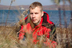 Young blond man in red jacket sit on the seashore. Royalty Free Stock Photos