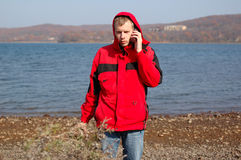 Young blond man in red jacket talk on mobile phone Stock Photos