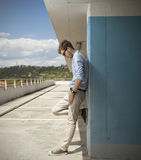 Young blond man on a roof. Young man looking down on roof parking Royalty Free Stock Photography