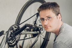 Young blond man with short haircut in a gray t-shirt with glasses sitting near spinning wheel of dirty broken bicycle. Portrait of young blond man with short stock photo