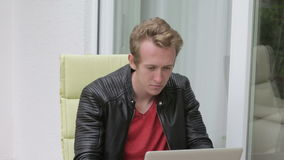 Young blond man sitting outside on balcony and typing on laptop stock video footage