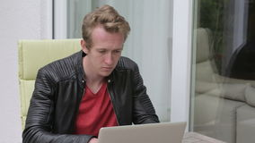 Young blond man sitting outside on balcony and typing on laptop stock video