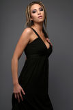 Young  blond model in black. Dress posing on grey background Stock Photo