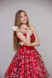 Young blond model with long hair in red dress with candy in hands smiling and having fun on gray background in studio Stock Photo