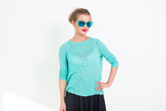 Young blond model posing in studio, performing new fashion glamour look, wearing sunglasses, putting her arm on the hip Royalty Free Stock Photos