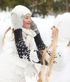 Young blond mother takes care of her daughter outdoors Royalty Free Stock Images