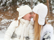 Young blond mother takes care of her daughter outdoors. Winter Royalty Free Stock Photo