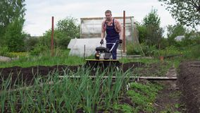 Young blond muscular farmer cultivates ground soil with rotary mini tiller. Side view of young blond muscular farmer cultivates ground soil with rotary mini stock footage