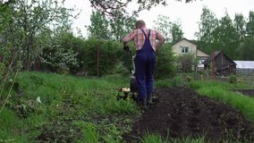 Young blond muscular farmer cultivates ground soil with rotary mini tiller. View from the back on young blond muscular farmer cultivates ground soil with rotary stock footage