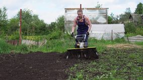 Young blond muscular farmer cultivates ground soil with rotary mini tiller. Young blond muscular farmer cultivates ground soil with rotary mini tiller before stock video