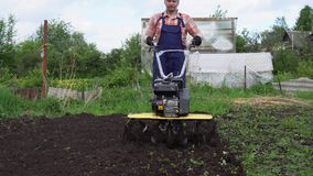 Young blond muscular farmer cultivates ground soil with rotary mini tiller. Young blond muscular farmer cultivates ground soil with rotary mini tiller before stock footage