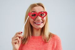 Young blond in paperheart shaped glasses. Studio portrait Stock Photo